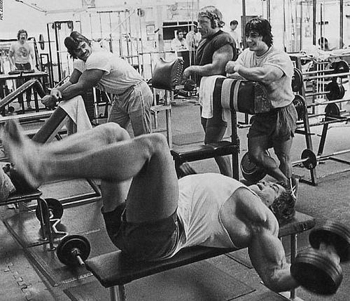 Arnold Schwarzenegger à l'écarté couché avec haltères