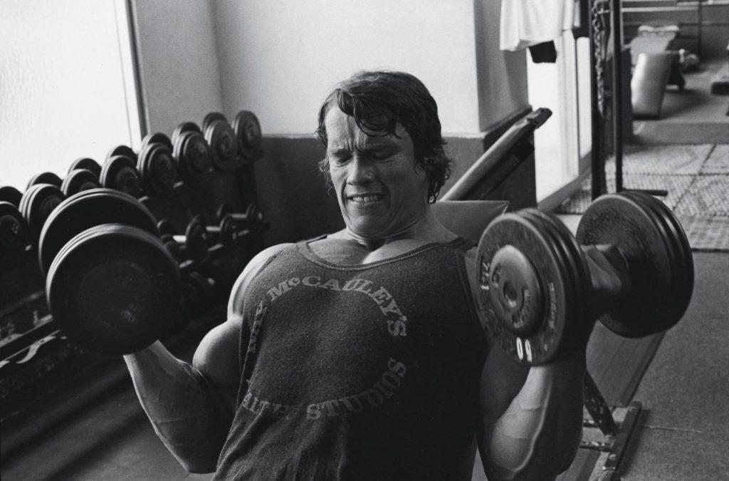 Arnold Schwarzenegger au curl incliné avec haltères
